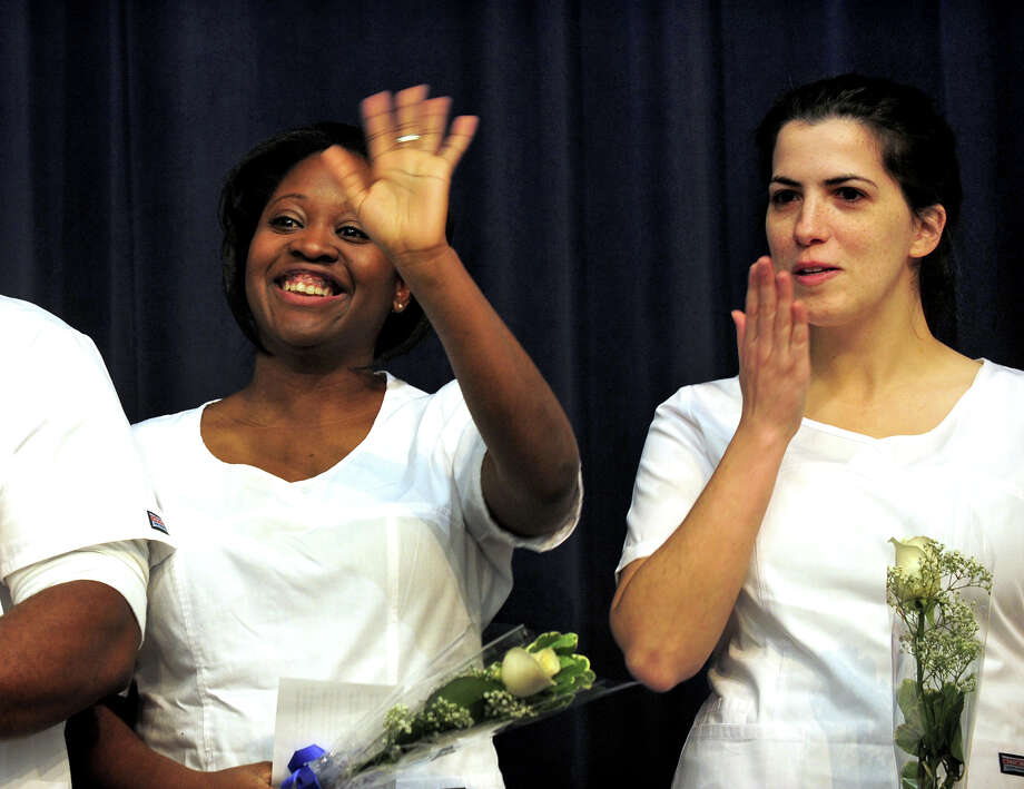 Graduating nurses Debbieann Brown-Davis and Amanda Cassidy, right, wave to family members during the Porter and Chester Institute's Pinning and Candle Lighting Ceremony for its first ever graduating class of nurses from its Stratford campus at Bunnell High School in Stratford, Conn. on Thursday January 23, 2014. Photo: Christian Abraham / Connecticut Post