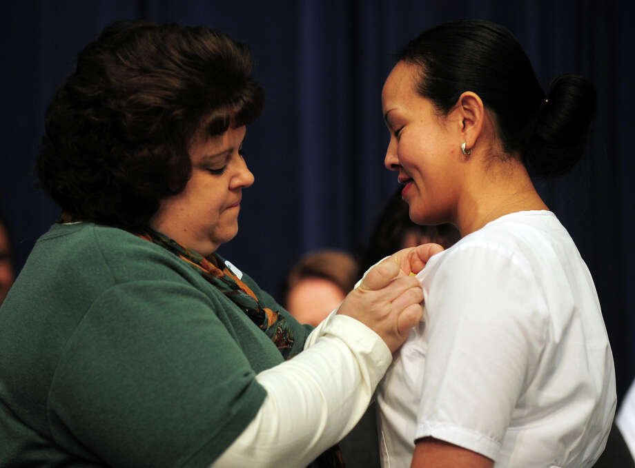 Kathleen Bhatti MSN RN, fastens a pin onto graduating nurse Vatsana Bratton, during a Pinning and Candle Lighting Ceremony for the Stratford campus of Porter and Chester Institute's first ever graduating class of nurses at Bunnell High School in Stratford, Conn. on Thursday January 23, 2014. Photo: Christian Abraham / Connecticut Post