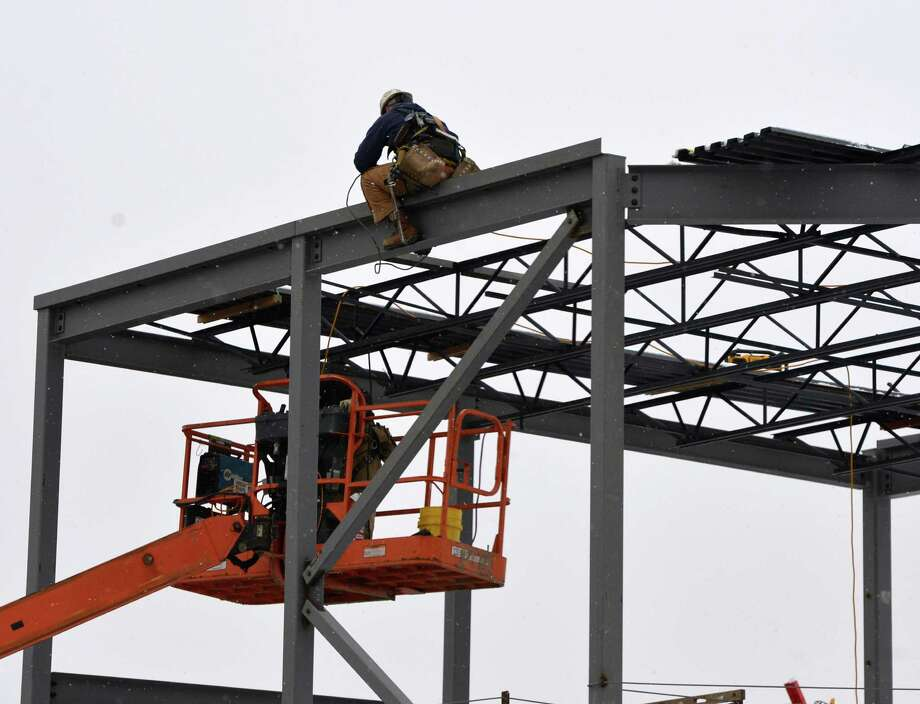 Steel workers put a beam in place as construction continues for the new Price Chopper at the former site of St. Patrick's Roman Catholic Church Monday morning Jan. 20, 2014, in Watervliet, N.Y.       (Skip Dickstein / Times Union) Photo: SKIP DICKSTEIN / 0025427A