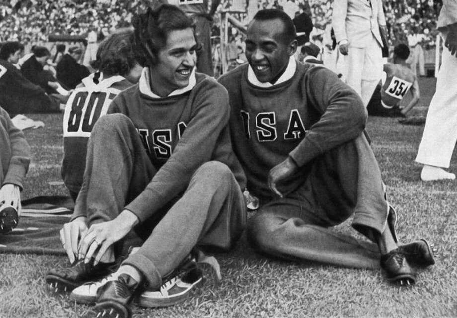 US champions Jesse Owens and Helen Stephens (L) chat together on the Berlin stadium during the opening of the Olympic Games where Owens captured 4 gold medals, 100m, 200m, 4x100m and long jump and Stephens captured 2 gold, 100m and 4x100m establishing a world record. (CORR/AFP/Getty Images) Photo: AFP, AFP/Getty Images / 2012 AFP