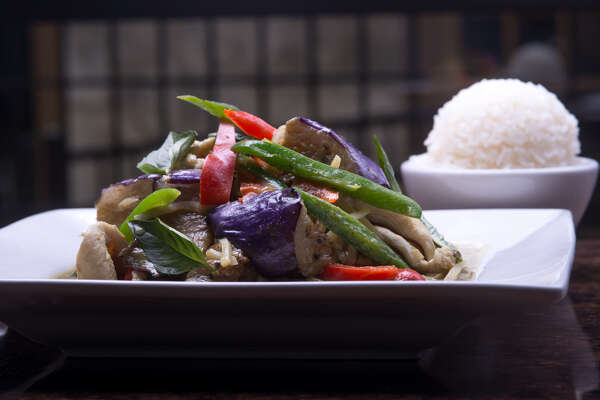 A colorful and tasty green curry is available in a range of heat levels. The hottest will burn, but still have good flavors.