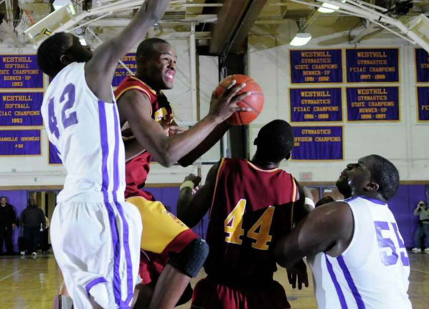 St. Joseph's #15 Timajh Parker cuts through traffic to head to the hoop among St. Joseph #44 Oscar Assie, Westhill #42 Sam Dorissaint and #55 Ervin Thompson as Westhill High School hosts St. Joseph High School in boys basketball in Stamford, CT on Friday, February 4, 2011.