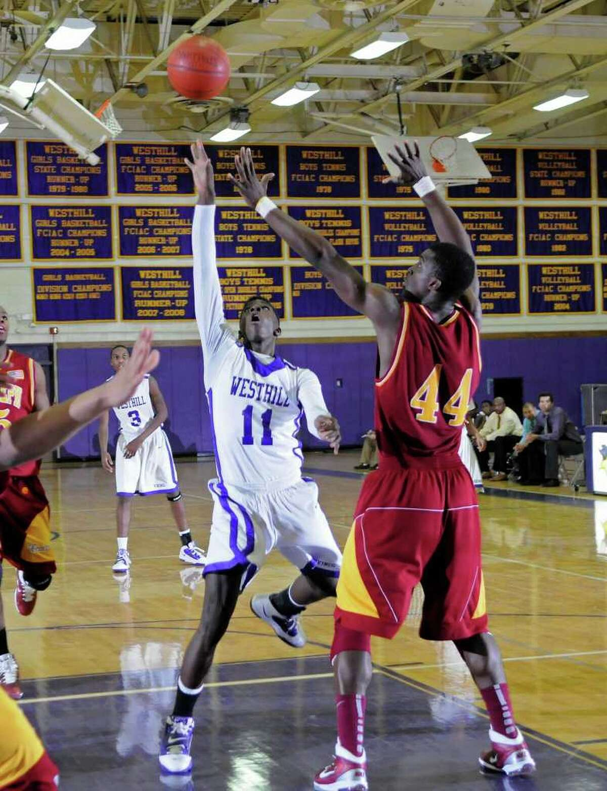 Westhill's #11 Antwaun Boyd takes a shot as St. Joe's #44 Oscar Assie steps in as Westhill High School hosts St. Joseph High School in boys basketball in Stamford, CT on Friday, February 4, 2011.