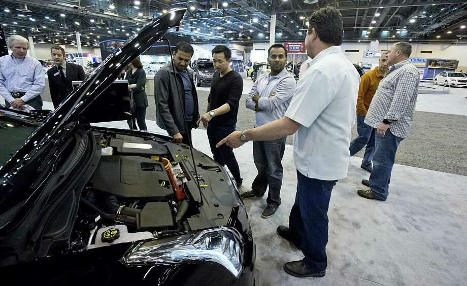 Hung Dang (wearing black, pointing) and friends look at the engine of the fully electric Cadillac ELR at the Houston Auto Show. The ELR can go 37 miles before dipping into gasoline reserves. Photo: Thomas B. Shea / Houston Chronicle / © 2013 Thomas B. Shea