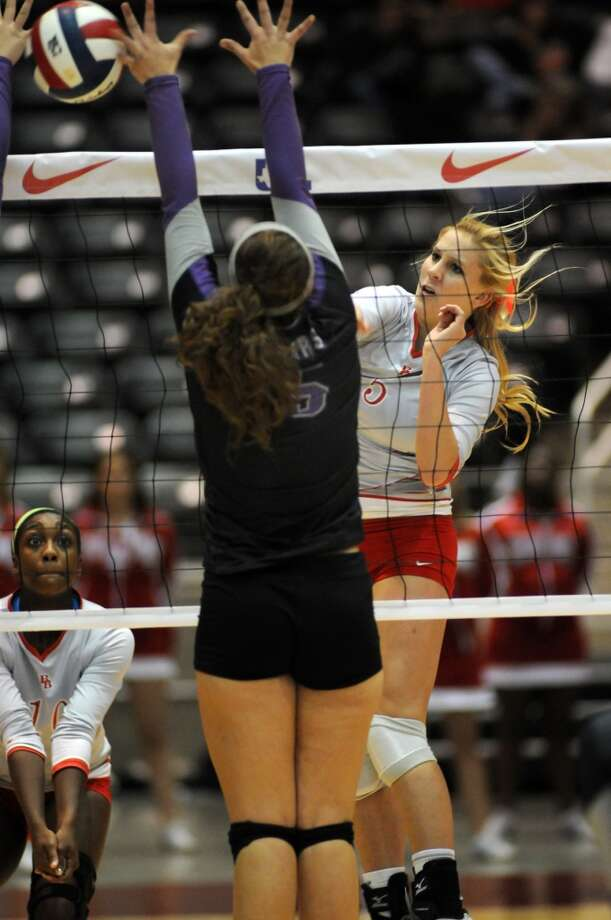 Bellville senior Lorin Robertson, right, sends a kill past a College Station defender during the Brahmanette's 4 set win over the Lady Cougars in the class 3A semifinals of the 2013 UIL Volleyball State Tournament at the Culver Center in Garland on Friday. Photo: For The Chronicle