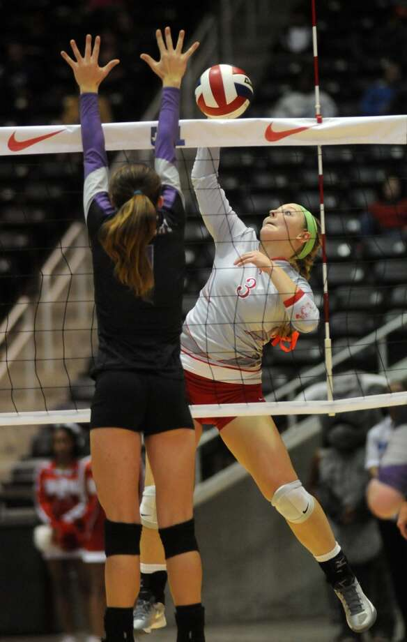 Bellville senior Briana Klotz, right, goes up for a kill past a College Station defender  in the semifinals of the 2013 UIL Volleyball State Tournament at the Culver Center in Garland on Friday. Photo: For The Chronicle