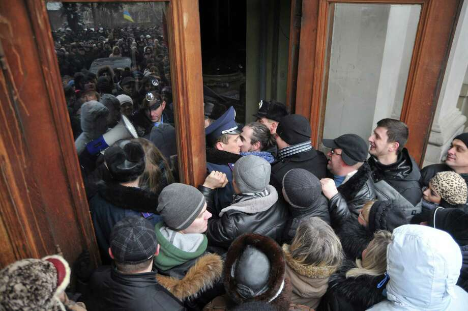 Protesters break into the building of the regional governor's office in Lviv, Western Ukraine, Thursday Jan. 23, 2014. Tensions in Ukraine spread far from its embattled capital on Thursday as hundreds of people in the city of Lviv stormed into the regional governor's office and forced him to write a letter of resignation. (AP Photo/Pavlo Palamarchuk) ORG XMIT: XEL111 Photo: Pavlo Palamarchuk / AP