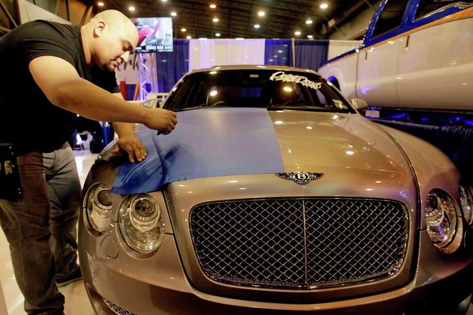 Gabe Garcia with Vinyl Werkz Customs demonstrates applying a piece of blue vinyl wrap to the hood of a Bentley at the Houston Auto Show in Reliant Center Thursday, Jan. 23, 2014, in Houston. The vinyl wrap used to customize a car can be removed without damage to the original paint. Photo: Melissa Phillip, Houston Chronicle / © 2014  Houston Chronicle