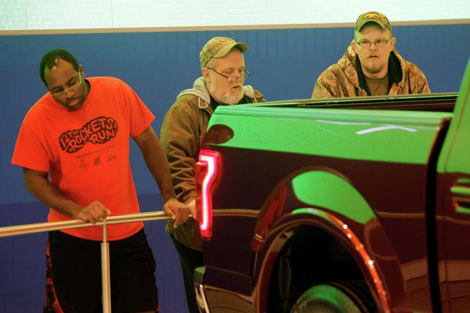Mark Munerlyn, left, of Houston, Pops McKinsey, center, of Alvin, and Cody McGee, right, of Danbury, look at a display of the Ford aluminum alloy F-150 during the Houston Auto Show in Reliant Center Thursday, Jan. 23, 2014, in Houston.  A green color is being reflected on part of the truck from a nearby video display. Photo: Melissa Phillip, Houston Chronicle / © 2014  Houston Chronicle