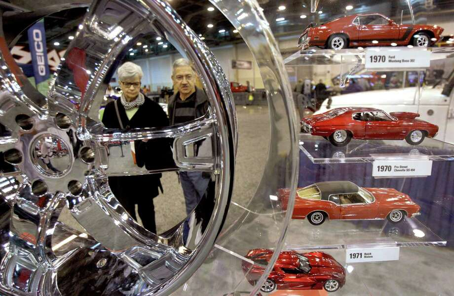 Dorothy Llorens and Clyde Llorens of Houston look at an exhibit during the Houston Auto Show. Photo: Melissa Phillip, Houston Chronicle / © 2014  Houston Chronicle