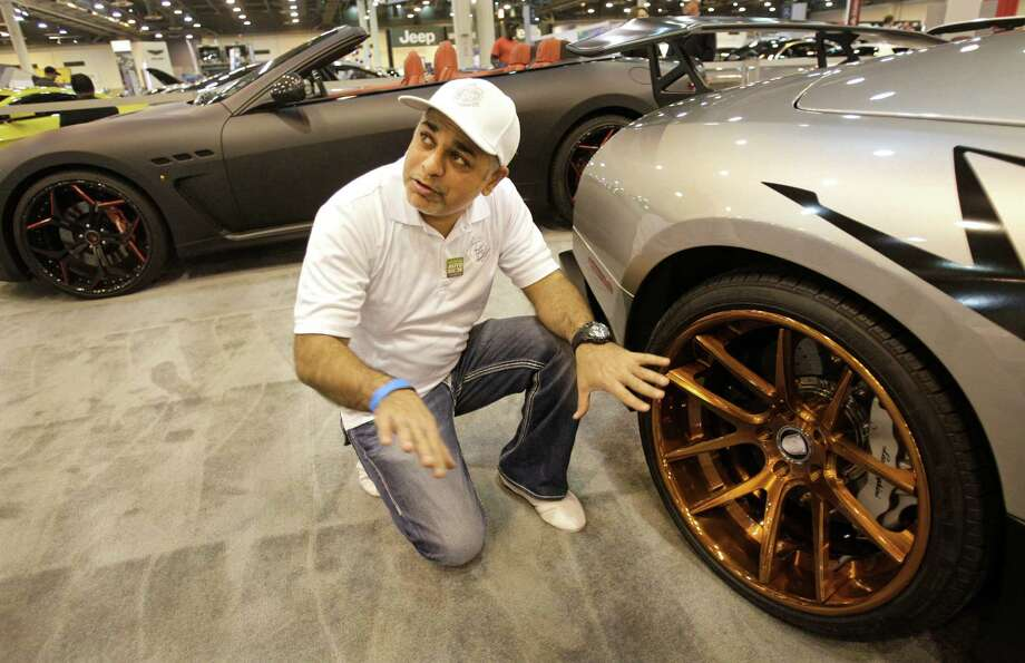 Taza Zohar, owner of Progressive Autosports, talks about their custom designed wheels, priced at $15,000 for four, shown on a Lamborghini SV in their display at the Houston Auto Show. Photo: Melissa Phillip, Houston Chronicle / © 2014  Houston Chronicle
