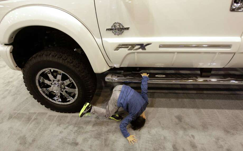 Enzo Barron, 4, of Houston takes a look underneath a Tuscany customized Ford truck at the Houston Auto Show. Photo: Melissa Phillip, Houston Chronicle / © 2014  Houston Chronicle