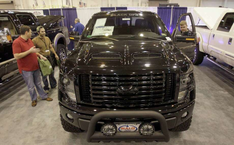 Car enthusiasts look at the customized Tuscany Ford F-150 Black Ops edition truck at the Houston Auto Show. Photo: Melissa Phillip, Houston Chronicle / © 2014  Houston Chronicle