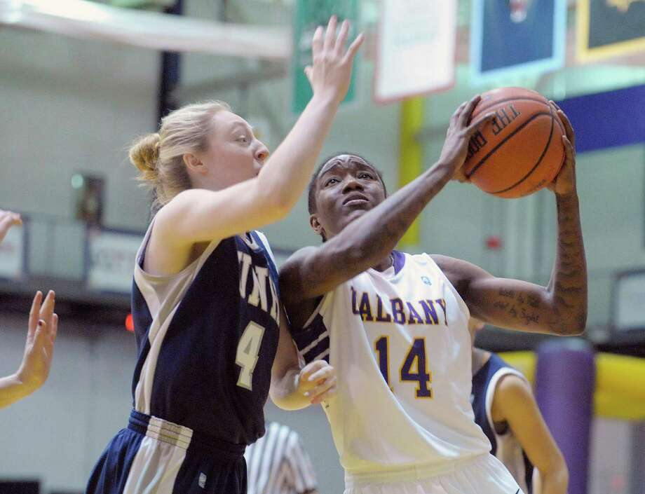 Kristen Anderson, left, of University of New Hampshire tries to stop Tammy Phillip of UAlbany as she drives towards the rim during their women's basketball game on Thursday, Jan. 23, 2014 in Albany, NY.   (Paul Buckowski / Times Union) Photo: Paul Buckowski / 00025453A