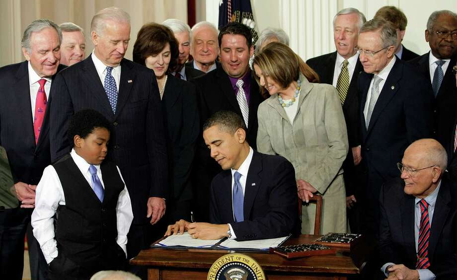 FILE - In this March 23, 2010, file photo, Marcelas Owens of Seattle, left, Rep. John Dingell, D-Mich., right, and others, watch as President Barack Obama signs the health care bill in the East Room of the White House in Washington. A closely watched survey says the nation's uninsured rate dropped modestly this month as the major coverage expansion under Obama's health care law got underway. The Gallup-Healthways Well-Being Index found that the uninsured rate for U.S. adults dropped by 1.2 percentage points in January, to 16.1 percent. The rate declined across major groups.  (AP Photo/J. Scott Applewhite, File) ORG XMIT: WX101 Photo: J. Scott Applewhite / AP