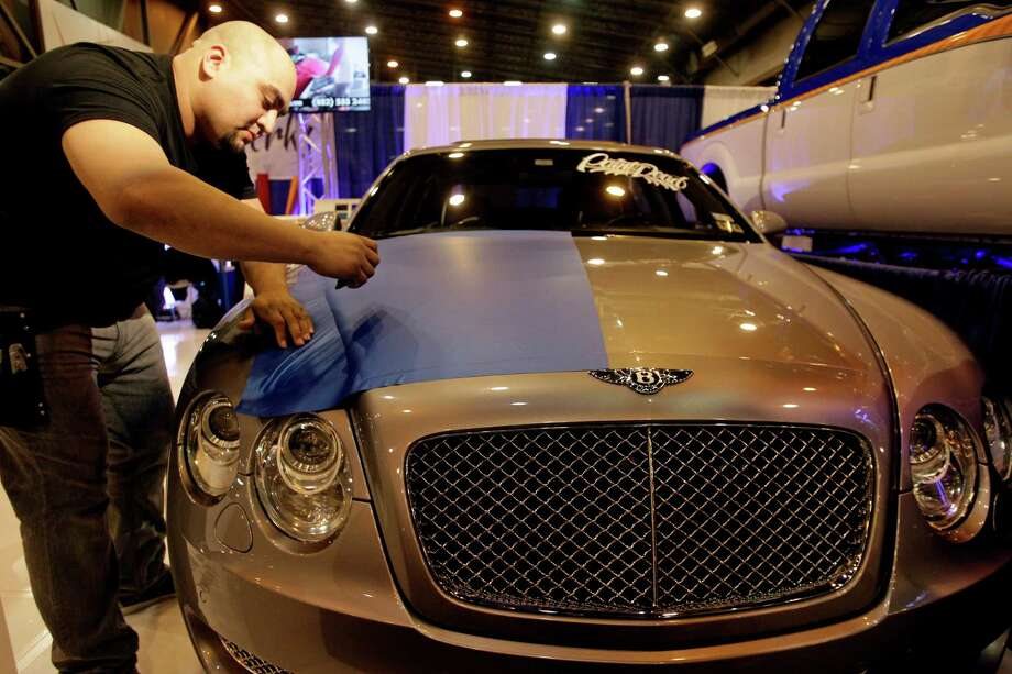 Gabe Garcia, co-owner of Vinyl Werkz Customs, shows how to apply a blue wrap to the hood of a Bentley at the auto show. Photo: Melissa Phillip, Staff / © 2014  Houston Chronicle