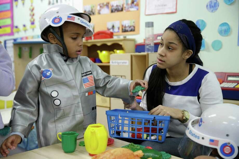 In this Tuesday, Jan. 21, 2014 photo, Bryson Payne, 4, left, and his teacher Jacqualine Sanchez play with pretend food in a pre-kindergarten class at the Sheltering Arms Learning Center in New York. Payne participated in a program that was produced in conjunction with Sesame Street to educate children about nutrition and health. (AP Photo/Seth Wenig) ORG XMIT: NYSW204 Photo: Seth Wenig / AP