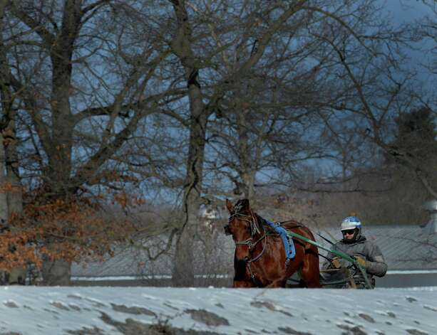 A harness racing trainer takes his charge out for some work in the relatively warm part of the day Thursday afternoon Jan. 23. 2014 at the Saratoga Raceway in Saratoga Springs, N.Y.    (Skip Dickstein / Times Union) Photo: SKIP DICKSTEIN