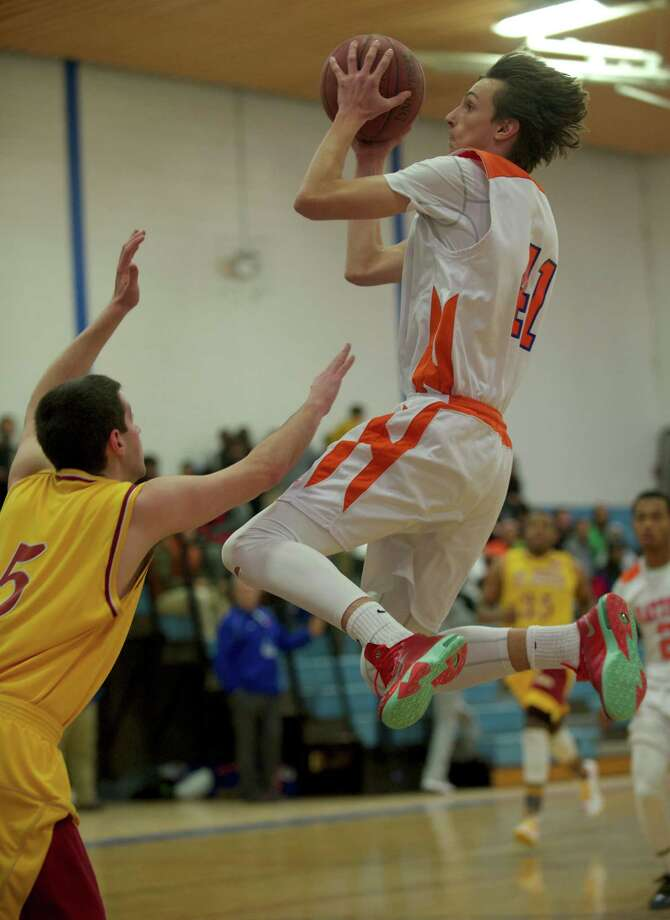 Danbury's Mike Kline, 41, goes up for a layup over St Joseph's Jon Dzurenda, 5, during a  boys FCIAC basketball game, St Josephs, of Trumbull, at Danbury High School, Danbury, Conn on Thursday, January 23, 2014. Photo: H John Voorhees III / The News-Times Freelance