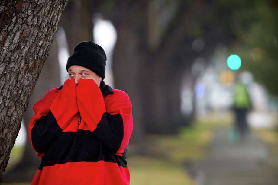 "Kat Allen takes cover under a tree, warming her hands near her face, while walking on Harrisburg near Eastwood Park Thursday, Jan. 23, 2014, in Houston. ""I can't believe how fast the temperature dropped,"" she said, as she tried to stay warm on her way home. ( Brett Coomer / Houston Chronicle ) Photo: Brett Coomer, Staff / © 2014 Houston Chronicle"
