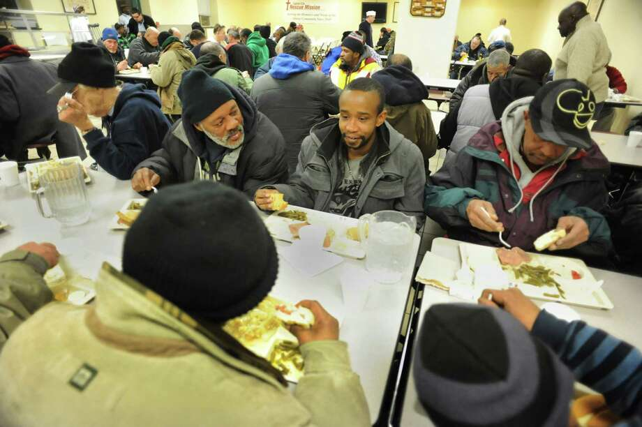 Dwayne Crawford, a Code Blue client, center, joins other homeless men for dinner on Thursday, Jan. 23, 2014, at Capital City Rescue Mission in Albany, N.Y. (Cindy Schultz / Times Union) Photo: Cindy Schultz