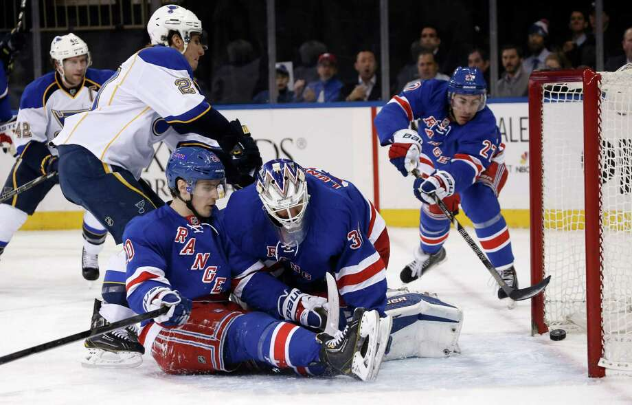 New York Rangers defenseman Ryan McDonagh (27) tries to save a goal scored by St. Louis Blues left wing Alexander Steen (20) as Rangers left wing Chris Kreider (20) collides with Rangers goalie Henrik Lundqvist (30), of Sweden, in front of the crease in the first period of an NHL hockey game at Madison Square Garden in New York, Thursday, Jan. 23, 2014. After review, the play was ruled a Blues goal credited to Steen. (AP Photo/Kathy Willens) ORG XMIT: MSG101 Photo: Kathy Willens / AP
