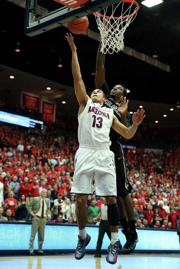 TUCSON, AZ - JANUARY 23:  Nick Johnson #13 of the Arizona Wildcats lays up a shot past Wesley Gordon #1 of the Colorado Buffaloes during the first half of the college basketball game at McKale Center on January 23, 2014 in Tucson, Arizona.  (Photo by Christian Petersen/Getty Images) ORG XMIT: 185392890 Photo: Christian Petersen / 2014 Getty Images