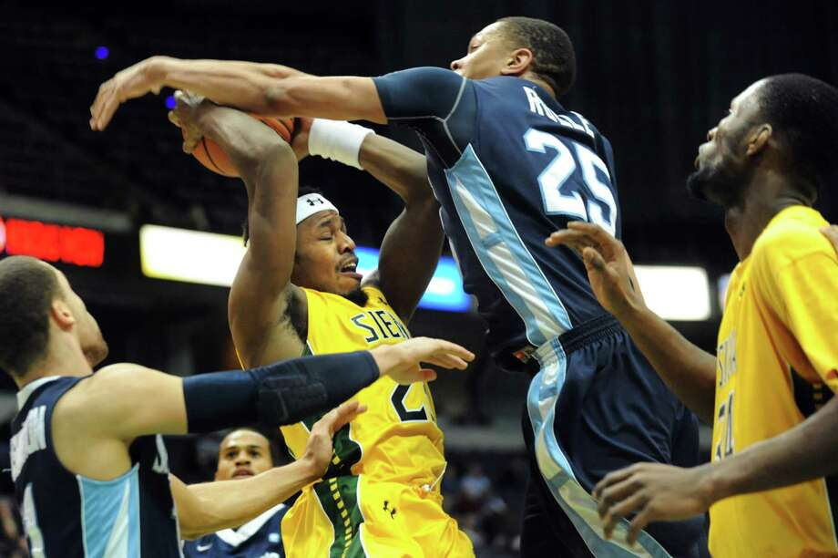Siena's Maurice White, center, fights for a rebound with St. Peter's Kris Rolle during their basketball game on Thursday, Jan. 23, 2014, at Times Union Center in Albany, N.Y. (Cindy Schultz / Times Union) Photo: Cindy Schultz / 00025450A