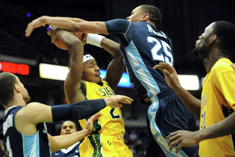 Siena's Maurice White, center, fights for a rebound with St. Peter's Kris Rolle during their basketb