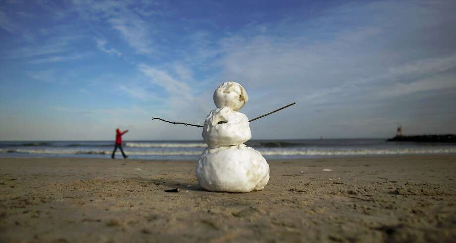 I'm doomed:A snowman on the beach at Rudee Inlet in Virginia Beach, Va, looks up at his mortal enemy. Photo: L. Todd Spencer, Associated Press