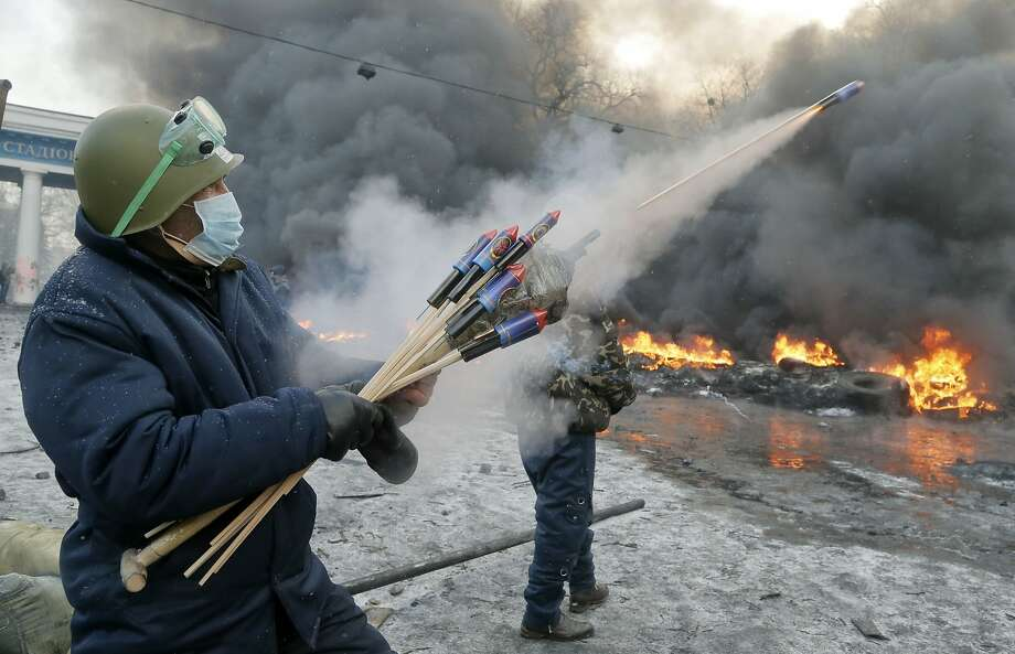 A protester aims fireworks at police during clashes, in central Kiev, Ukraine, Thursday, Jan. 23, 2014. Thick black smoke from burning tires engulfed parts of downtown Kiev as an ultimatum issued by the opposition to the president to call early elections or face street rage was set to expire with no sign of a compromise on Thursday.  (AP Photo/Efrem Lukatsky) Photo: Efrem Lukatsky, Associated Press