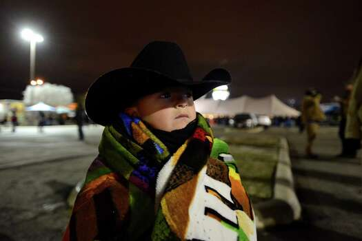 Brian Longoria, 5, keeps warm in frigid weather during the 36th Cowboy Breakfast in the parking lot of Cowboys Dance Hall on Friday, Jan. 24, 2014. The event unofficially kicks off the San Antonio Stock Show & Rodeo. Photo: Billy Calzada, San Antonio Express-News / San Antonio Express-News