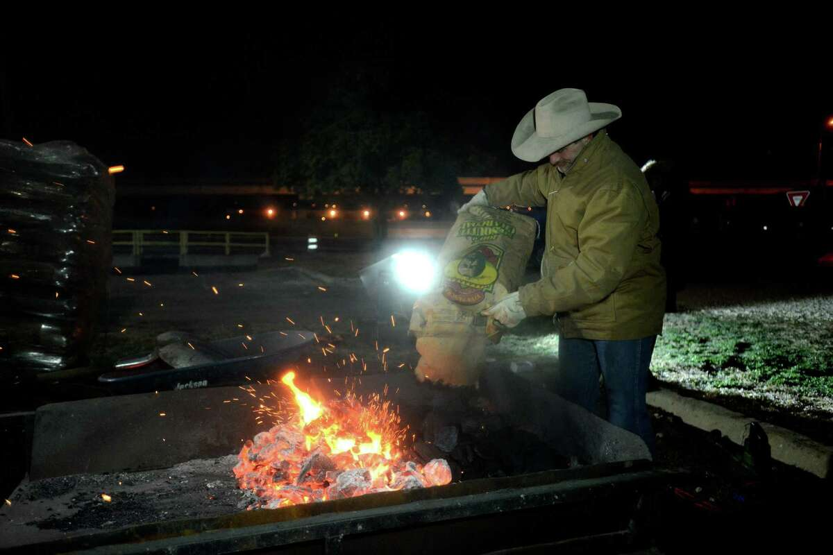A fire for cooking taco ingredients is nursed during the 36th Cowboy Breakfast in the parking lot of Cowboys Dance Hall on Friday, Jan. 24, 2014. The event unofficially kicks off the San Antonio Stock Show & Rodeo.