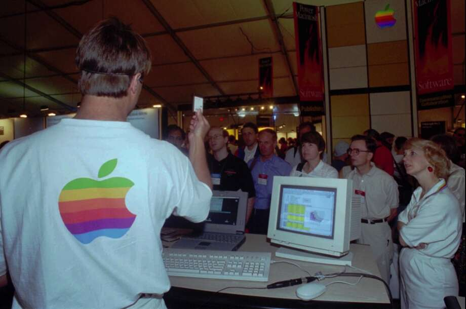 John Maletic, employee from Apple Computer Inc., left, demonstrates the usage of a Macintosh computer product at the annual Macworld Expo on August 3, 1994. Photo: KUNI TAKAHASHI, Associated Press