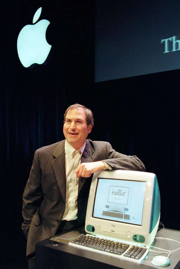 "Steve Jobs, then-interim CEO, poses with a new iMac during a media event on May 6, 1998. This all-in-one computer had a new look.""Up until then all of our computers were either battleship grey or an off-white cream color,"" Bajarin said. ""No one had thought of purple, blue, or orange as a computing design. That really caught people's attention."" Photo: John G. Mabanglo, AFP/Getty Images"