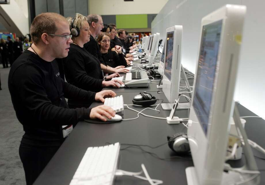 Apple workers use  iMacs at the MacWorld conference in a San Francisco on Jan. 10, 2006. Photo: PAUL SAKUMA, AP Photo