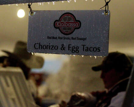Volunteers cook up breakfast by a taco sign with icicles hanging off of it Friday January 24, 2014 at the annual Cowboy Breakfast at the parking lot of Cowboys Dancehall. Photo: JOHN DAVENPORT, SAN ANTONIO EXPRESS-NEWS / ©San Antonio Express-News/Photo may be sold to the public