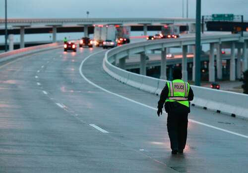 Police guide vehicles slowly backward on the icy ramp to Hwy. 290 to Beltway 8 early Friday morning. Photo: Johnny Hanson, Houston Chronicle