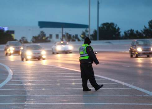 Police guide southbound Beltway 8 traffic away from the Hwy. 290 on-ramp early Friday morning. Photo: Johnny Hanson, Houston Chronicle