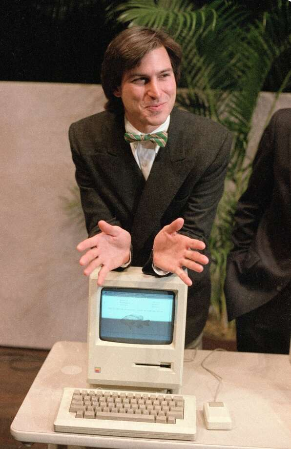 """Steve Jobs leans on the new Macintosh personal computer following a shareholder's meeting on Jan. 24, 1984, in Cupertino.He pulled the device out of a case, turned it on, and stood aside as the computer displayed a series of images.  """"We've done a lot of talking about Macintosh recently,"""" he said afterward. """"But today for the first time ever, I'd like to let Macintosh speak for itself.""""The computer said, """"Hello, I'm Macintosh. It sure is great to get out of that bag."""" Photo: Paul Sakuma, Associated Press"""