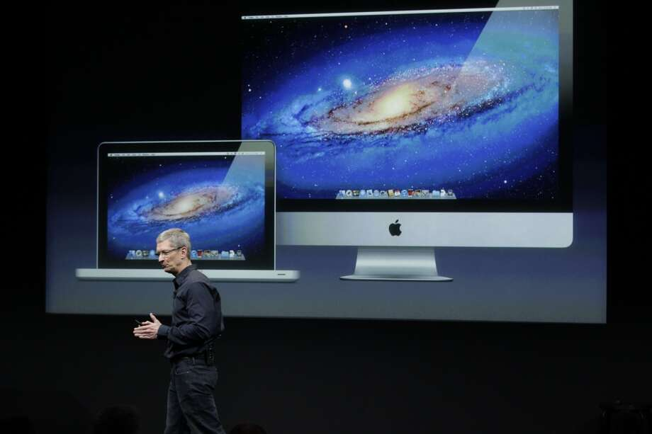 In his first keynote as CEO, Tim Cook speaks in front of a projection of the Macbook Air and iMac during an announcement at Apple headquarters on Oct. 4, 2011. Photo: Paul Sakuma, ASSOCIATED PRESS