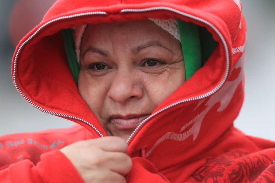 Mari Carmen Flores tries to stay warm on Jan. 24, 2014.  ( Mayra Beltran / Houston Chronicle )