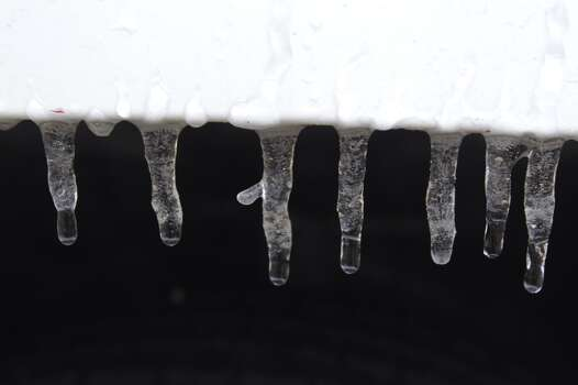 Icicles are shown hanging on the fender of a truck Friday, Jan. 24, 2014, in Spring.  ( Melissa Phillip / Houston Chronicle )