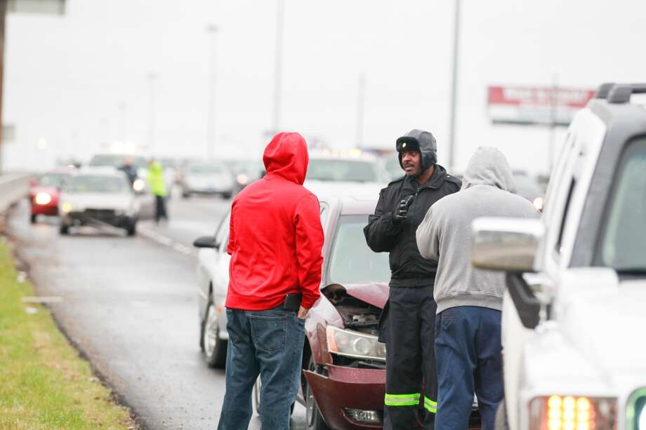 A police officer talks to those involved in a three car accident on Hwy. 290 near Beltway 8. (Johnny Hanson /  Houston Chronicle)