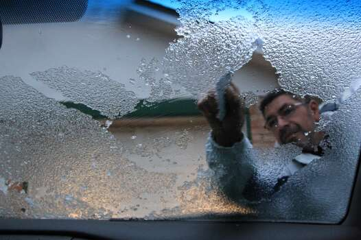 Rafael Ortega is busy scrapping ice from windshield with a credit card before heading out to work this morning on Jan. 24, 2014.  ( Mayra Beltran / Houston Chronicle ) Photo: Mayra Beltran, Houston Chronicle