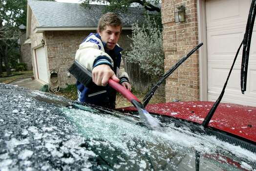 Colton Whitefield scrapes the ice off his dad's car on Friday Jan. 24, 2014 as cold temperatures returned to the area.  Icy conditions caused school and road closures throughout the area Photo: Helen L. Montoya, SAN ANTONIO EXPRESS-NEWS / SAN ANTONIO EXPRESS-NEWS