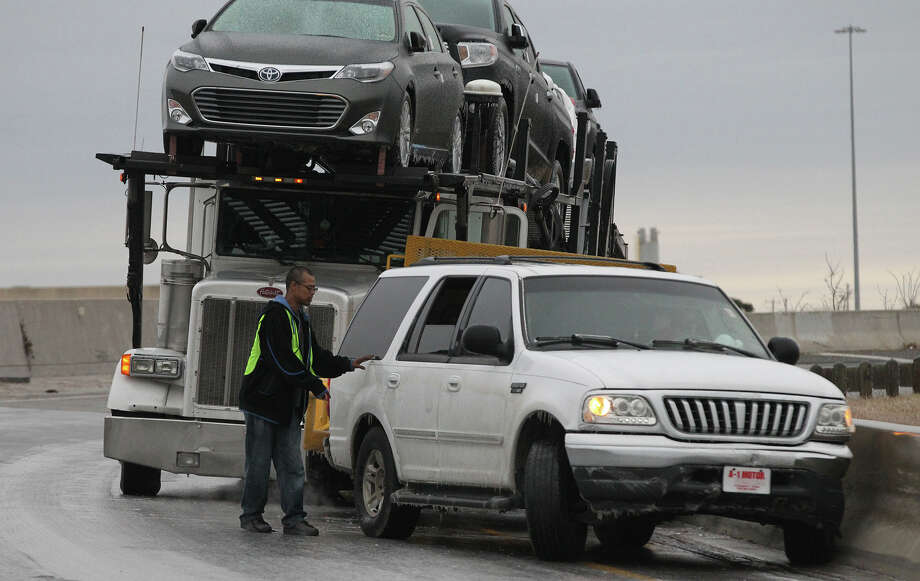 A tractor trailer rig and an SUV are lodged against the side barrier of the southbound interchange of Loop 410 and IH-35 southbound. Most highway bridges and interchanges were coated with ice Friday January 24, 2014. Photo: JOHN DAVENPORT, SAN ANTONIO EXPRESS-NEWS / ©San Antonio Express-News/Photo may be sold to the public