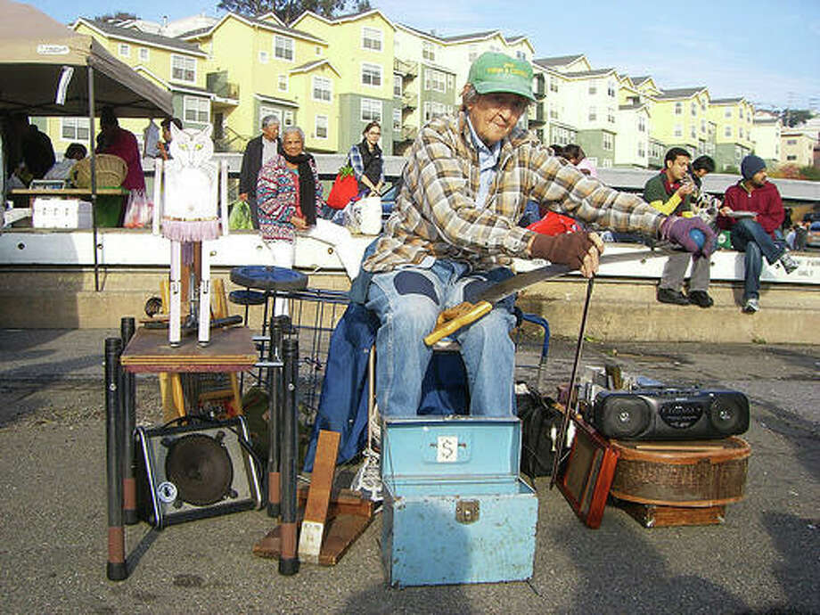 Watch Jackie Floyd Jones perform swinging 1920s tunes on her musical saw and guitar with her pal, a dancing pink wooden cat, at the Saturday Alemany Farmer's Market. Photo: Laughingsquid.com, Todd Lappin