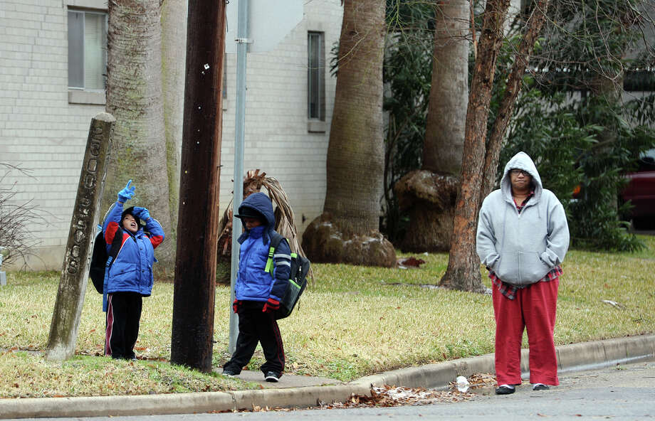Brothers Kelton, 3, and Elton Jolviet, 5, left and center, wait for their late bus while Leatha Hickman, right, keeps watch Friday morning. Freezing temperatures and overnight precipitation caused school delays and left icy markings on southeast Texas on Friday morning. Photo taken Friday, 1/24/14 Jake Daniels/@JakeD_in_SETX Photo: Jake Daniels / ©2013 The Beaumont Enterprise/Jake Daniels