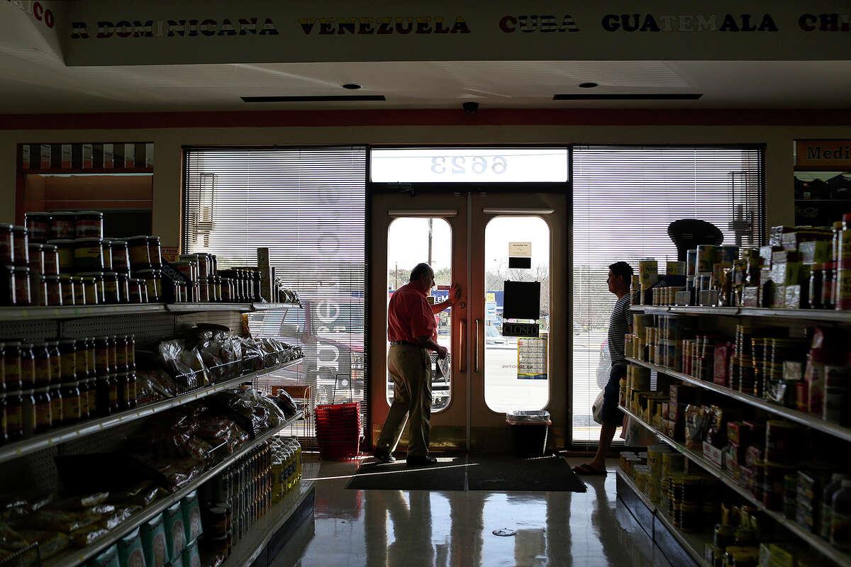 Jaime Jaramillo opens the door for a customer at Las Americas Latin Market in San Antonio on Friday, Jan. 17, 2014.